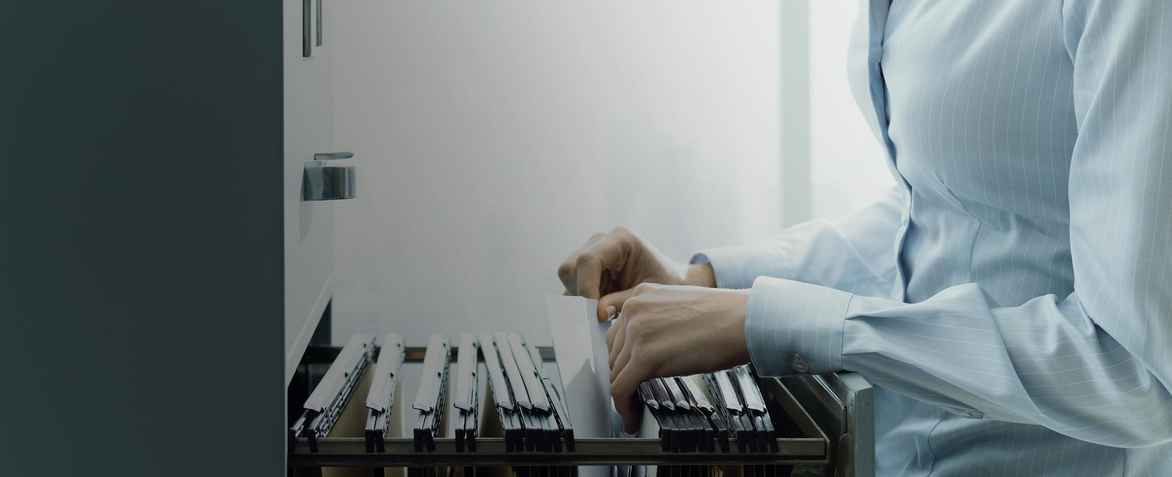 Professional looking through files in a filing cabinet