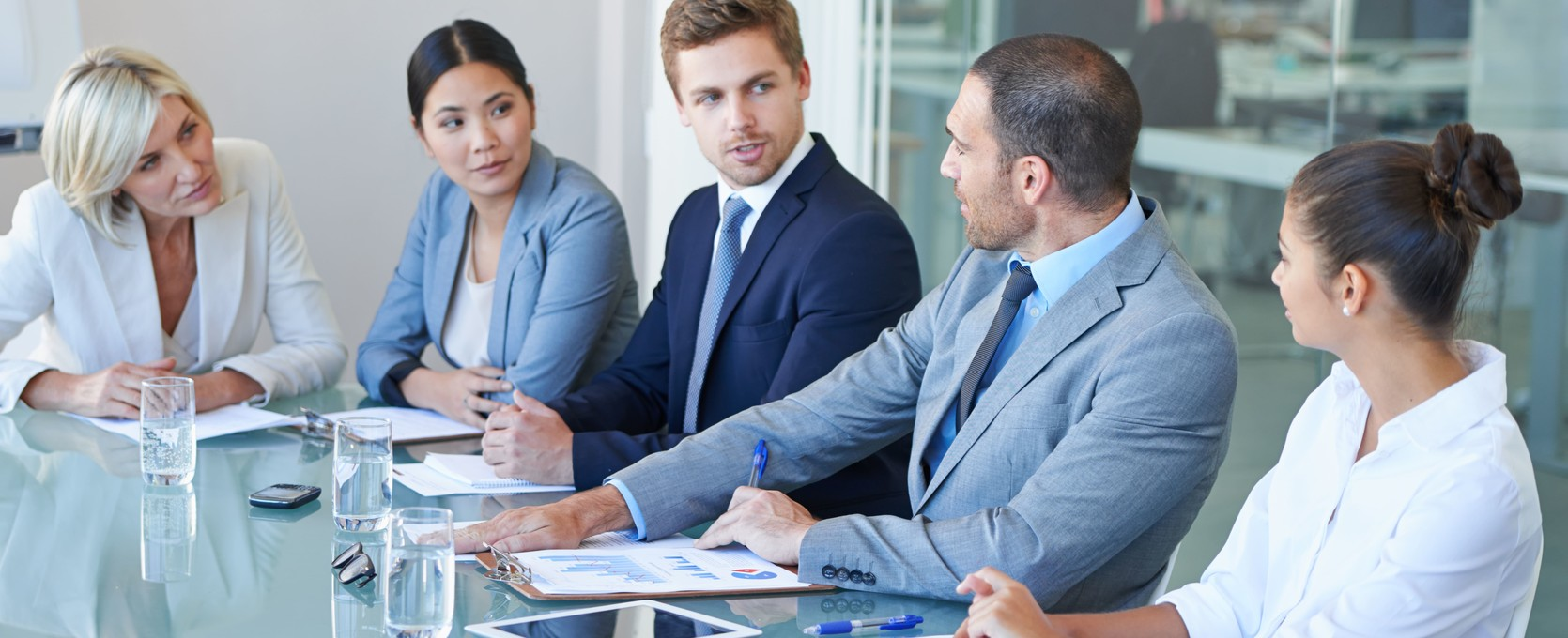 Young professionals gathered around in a conference room for a collaborative meeting